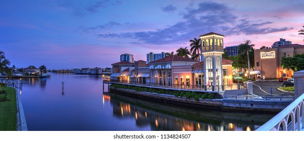 Naples, Florida, USA – July 14, 2018: Sunset over the colorful shops of the Village on Venetian Bay in Naples, Florida. Editorial use.