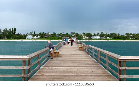 Naples, Florida, USA - July 24, 2016: View from Naples Pier on the coast. Naples Pier - popular spot for fishing and sunset views. People making landscape photo. Rest and vacation concept