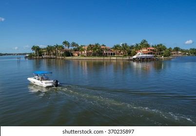 NAPLES, FLORIDA USA - May 8 2013: Rental Boat Cruising Past Large Luxury Waterfront Mansion in the Bayside area of Naples. Naples is one of the wealthiest cities in the United States