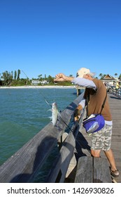 Naples, FL/USA: Feb 28, 2019 - Unidentified fisherman on Naples Pier in Florida catches catfish, scientific name Siluriformes, with barbels like whiskers. Beach and luxury housing in background.