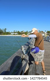 Naples, FL/USA: Feb 28, 2019 - Fisherman on Naples Pier in Florida catches catfish, scientific name Siluriformes. Beach and high end housing in background.