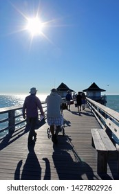Naples, FL/USA: Feb 28, 2019 - Visitors with fishing equipment walk on classic landmark The Pier, popular for exquisite sunsets and boatless fishing, as blazing sun begins to set in cloudless blue sky