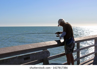 Naples, FL/USA: Feb 28, 2019 - Fisherman with grey hair on Naples Pier in Florida at dusk handles his fishing rod in cloudless blue sky as setting sun sparkles on Gulf of Mexico.