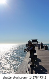 Naples, FL/USA: Feb 28, 2019 - Visitors with fishing equipment stand on landmark The Pier, popular for exquisite sunsets and boatless fishing, as blazing sun begins to set in the cloudless blue sky.