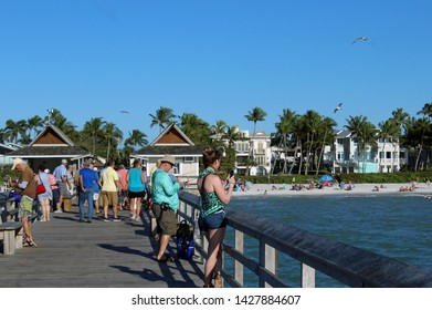Naples, FL/USA: Feb 28, 2019 - Visitors and fishermen stand on The Pier, known for exquisite sunsets and fishing. Sandy beach, swimmers, sunbathers, palm trees and luxury housing in background.