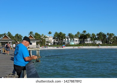 Naples, FL/USA: Feb 28, 2019 - Fisherman stands on The Pier, known for exquisite sunsets and fishing. Sandy beach, swimmers, sunbathers, palm trees and luxury housing in background.