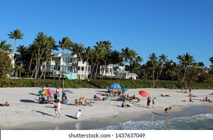 Naples, FL/USA: Feb 28, 2019 –Sunbathers and swimmers relax on beach. Cloudless blue sky, sandy beach and high end oceanfront housing in background.