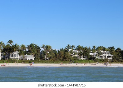 Naples, FL/USA: Feb 28, 2019 –View from Gulf of Mexico as sunbathers and swimmers relax on beach in upscale Naples FL. Cloudless blue sky, sandy beach and high end waterfront housing in background.
