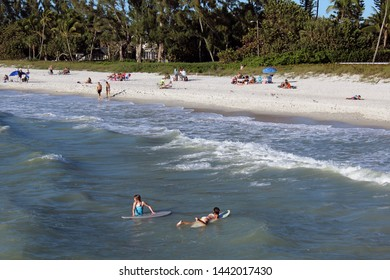 Naples, FL/USA: Feb 28, 2019 –Two girls on surfboards relax in Gulf of Mexico in upscale Naples FL with sunbathers, swimmers, trees, and sandy beach in background.