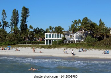Naples, FL/USA: Feb 28, 2019–View from Gulf of Mexico as sunbathers and swimmers relax on beach in upscale Napes FL. Cloudless blue sky, sandy beach and architecturally interesting waterfront housing.