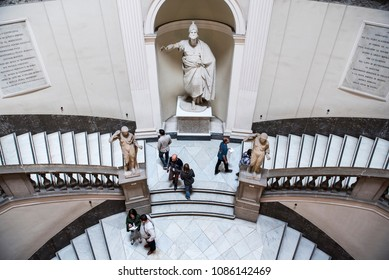 Naples, Italy - April 18, 2018. Visitors walk inside the Archaeological Museum of Naples, next to a statue.