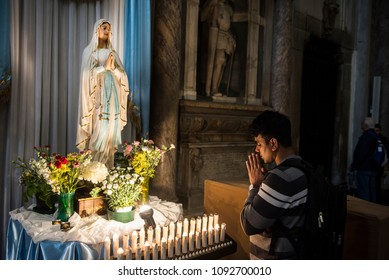 Naples, Italy - April 18, 2018. A young man prays a statue of Virgin Mary, inside the Naples Cathedral or Cathedral di San Gennaro, with beautiful early morning light.