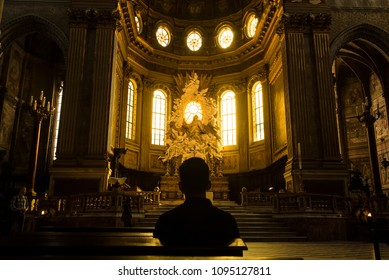 Naples, Italy - April 18, 2018. Silhouette of a man sitting inside the Naples Cathedral or Cathedral di San Gennaro, with beautiful early morning light.