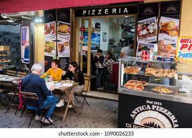 Naples, Italy - April 19, 2018. People eat pizza at a pizzeria inside the old city of Naples.