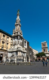 Naples, Italy - April 6, 2019: The obelisk of the Immaculate is a Baroque obelisk of Naples located in Piazza del Gesù Nuovo, opposite the church of the same name.