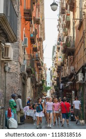 Naples, Italy - August 9, 2015: Ordinary people and tourists walk on narrow street, old town of Naples