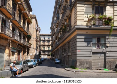 Naples, Italy - August 9, 2015: Street view of Naples, ordinary man sits near parked cars