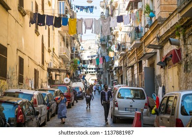 NAPLES, ITALY - CIRCA OCTOBER, 2017: View of residents walking down a typical congested laundry-lined street of the historic center.