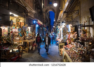 NAPLES, ITALY - CIRCA OCTOBER, 2017: Pedestrians pass displays of traditional Neapolitan nativity scenes called presepi on the narrow Via San Gregorio Armeno, also known as Christmas Alley.