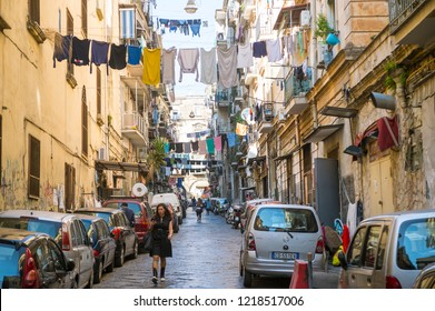 NAPLES, ITALY - CIRCA OCTOBER, 2017: Clothes hang from laundry lines strung over pedestrians walking on the narrow streets of the historic city center.