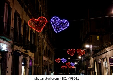 "Naples, Italy - February 09 2018: Valentines day illuminated hearts on the city streets. ""Chiaja in Love"" project with neon lit hearts at Chiaja neigborhood shopping streets in Napoli at night."