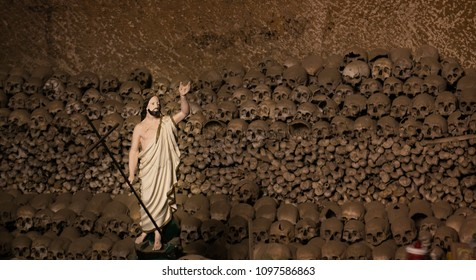 Naples / Italy - February 2018: Sculpture of Jesus in the front of a wall made of skulls and bones. Recorded at the Fontanelle Cemetery in Naples.