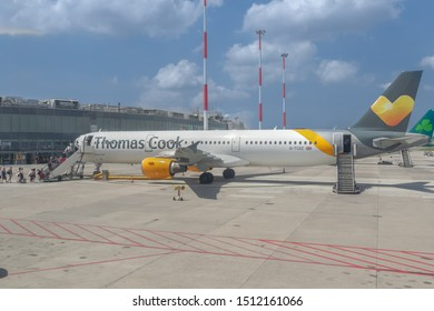 Naples, Italy - July 19 2019: Thomas Cook Airbus A 321 taxied on airport runway tarmac with boarding passengers and logo on wing. Company declared bankruptcy on Monday 23 September 2019.
