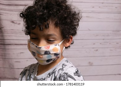 Naples Italy July 20, 2020 Hispanic child wears a medical mask or surgical mask to protect him from viruses, diseases, Covid-19, and coronavirus infection.