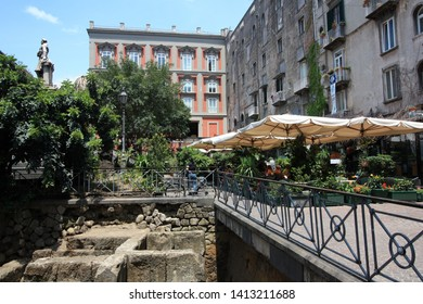 Naples, Italy - June 12th 2011: People enjoying life underneath sunshades of a café at Piazza Bellini in Napoli, Italy, right next to some excavations from the ancient Roman Empire