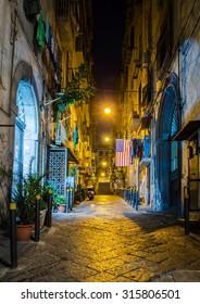NAPLES, ITALY, JUNE 28, 2014: night view of illuminated street leading through the historical center of italian city naples - napoli.