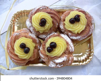 Naples, Italy - March 19, 2016: zeppole of Saint Joseph, Italian pastry  with flour, sugar, eggs, olive oil, custard, decorated with a sour cherry. Father's Day cake. I've done some correction