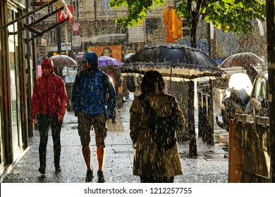 Naples, Italy - October 2018: People walking under umbrella during heavy rain
