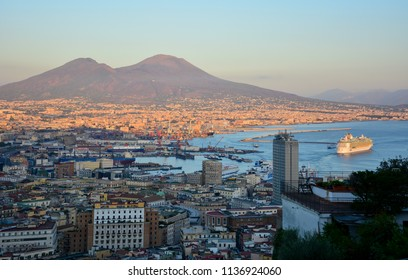 Naples / Italy — September 15, 2017: skyline of Naples at sunset with a ship in the port and the Mount Vesuvius in the background