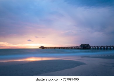 Naples pier beach and calm ocean during sunset, Florida, USA. Amazing cloudscape after a big tropical storm in the Gulf of Mexico, close to Everglades National Park.