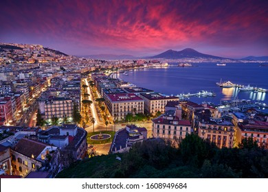 Naples, twilight evening pink violet sunset. Town Napoli in Italy, travelling in the Europe. Urban landscape with city, sea, hills and Vesuvio Volcano. Beautiful sunset sky, end of the day.