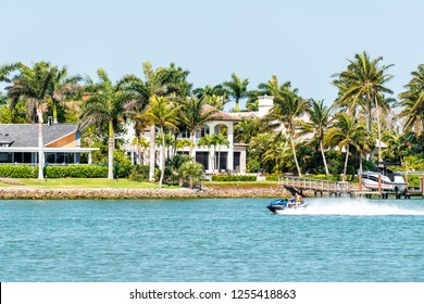 Naples, USA - April 30, 2018: Nelson's Walk house buildings with water on Dollar bay, palm trees, blue sky in residential community, people on boat in Florida