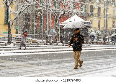 Naples,Italy- February 27, 2018: A man walking on the road under the snowfall with umbrella. Incredible atmospheric phenomenon in Naples. Abundant snowfall that was not seen since 1956.