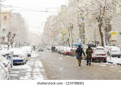 Naples,Italy- February 27, 2018:People walking under the snowfall with umbrellas. Incredible atmospheric phenomenon in Naples. Abundant snowfall that was not seen since 1956.