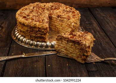 Napoleon cake with custard is decorated with raisins and grated chocolate on a silver platter on a wooden table. Dessert Napoleon cake is chopped. Cake Napoleon close-up.
