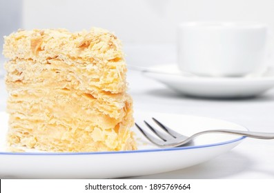 Napoleon Cake on a white plate. Traditional French dessert. Cake Napaleon of puff pastry on white background.