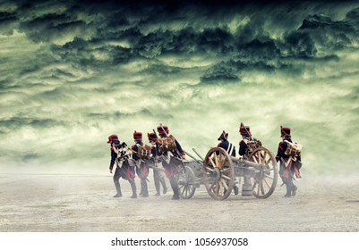 Napoleon soldiers marching in open land with a cannon.