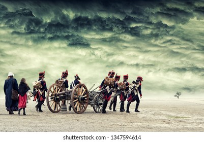 Napoleonic soldiers marching in open land and pulling a cannon, gun. Dramatic landscape with stormy clouds