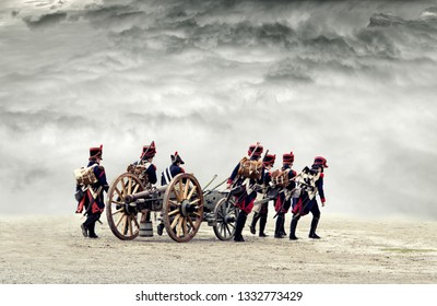 Napoleonic soldiers marching in open plain land with dramatic clouds., pulling a cannon.