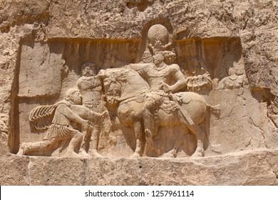 Naqsh-e Rustam, Iran - April 2016.  Bas-relief of the Persian Empire. Rock relief of the triumph of Shapur I over the Roman emperors Valerian and Philip the Arab