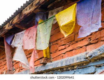 Nar village, Annapurna Conservation Area, Nepal - July 21, 2018 : Traditional buddhist prayer flags over tibetan architecture background, are used to bless the countryside and to promote peace