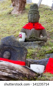NARA, JAPAN - JANUARY 10: Stone Buddha statue in Nara, Japan on January 10, 2013. Buddha statues are decorated in red material. Japanese believe that colour red symbolise the sun.