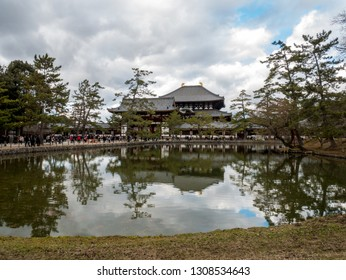 Nara, Japan - January 2, 2019 : Tourists going to Todai-ji temple (reflected in the pond) in Nara Park