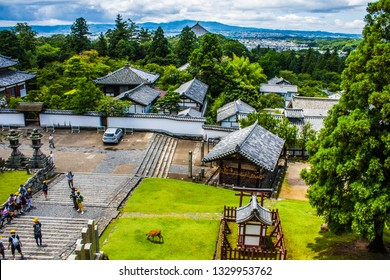 NARA, JAPAN - JUNE 23, 2016 : Bright and colorful aerial view of landscape and rooftops from the balcony,deck at Nigatsu-do Hall above the Todai-ji temple complex in Nara, Japan.People climbing stairs