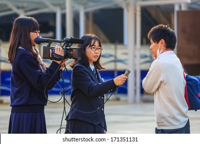NARA, JAPAN - NOVEMBER 16: Japanese Students in Nara, Japan on November 16, 2013.  Unidentified Japanese students with camera have a workshop of interviewing people at Nara Station
