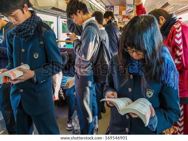 NARA, JAPAN - NOVEMBER 16: Japanese Students in Nara, Japan on November 16, 2013. Japanese students read their books for their examinations on a train to school